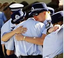 Lean on me ... grieving colleagues comfort each other. Photo: Liam Driver