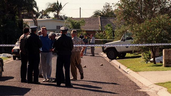 The scene in Walker Street, Crescent Head, the morning of the shootings, with the body of gunman John McGowan (right) covered by a sheet as police speak with shocked residents.