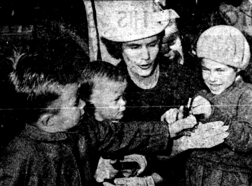Above: Mrs. Howe and her children. Mark, 4, Paul, 2, and Kim, 5, proudly examine the medal after the presentation.