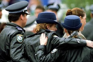 Uniformed police link arms at funeral of colleague Senior Constable Addison.
