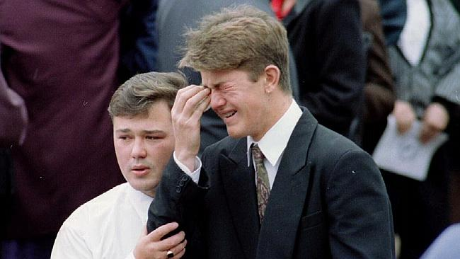 Glen Addison weeps as his brother Scott consoles him at their father's funeral.