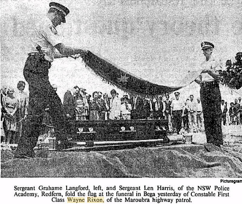 Sergeant Grahame Langford, left, and Sergeant Len Harris, of the NSW Police Academy, Redfern fold the flag at the funeral in Bega yesterday of Constable First Class Wayne Rixon, of the Maroubra highway patrol.