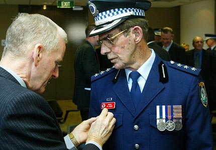 Fair cop ... Inspector Les Walker gets help with his medals from the former inspector Maurice Green. Photo: Peter Morris
