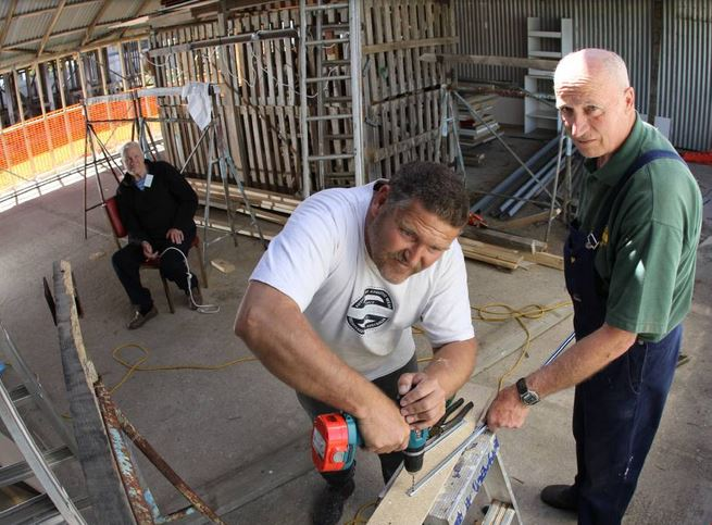 SAD LOSS: John Westergreen and Bob Payton work on the extensions to the Central Coast Community Shed. Looking on is John's father, Frank. Mr Payton was killed in a road accident on Saturday. Picture: Grant Wells.