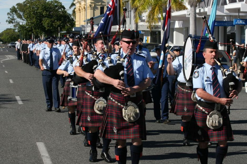The Queensland Police Pipes and Drums led the march to remember Norm Watt.