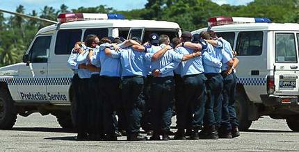 AFP officers farewell their mate Adam Dunning after loading his coffin into a RAAF jet at Honiara Domestic Airport. Photo: Andy Zakeli