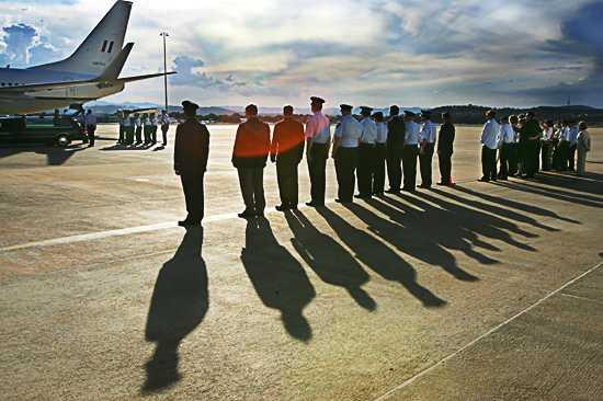 Senior officers and other dignatories, along with family members, watch Adam Dunning's coffin being loaded from the aircraft to a hearse at the RAAF Base at Fairbairn in Canberra. Photo: Andrew Taylor