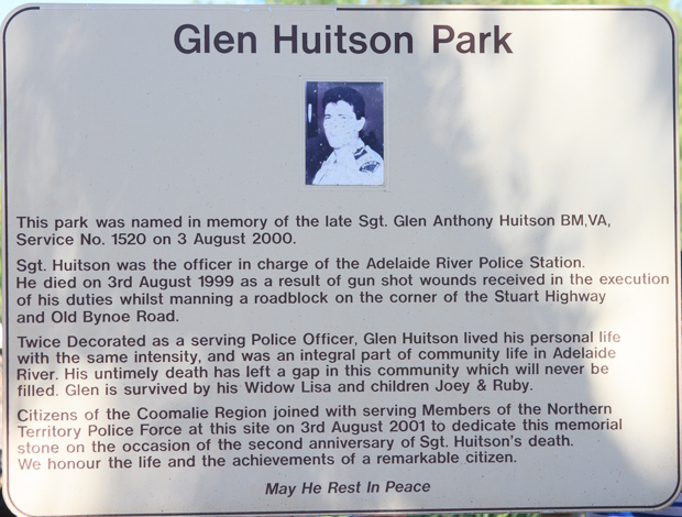 Front Inscription  Glen Huitson Park  This park was named in memory of the late Sgt. Glen Anthony Huitson BM,VA, Service No. 1520 on 3 August 2000.  Sgt. Huitson was the officer in charge of the Adelaide River Police Station. He died on 3rd August 1999 as a result of gun shot wounds received in the execution of his duties whilst manning a roadblock on the corner of the Stuart Highway and Old Bynoe Road.  Twice Decorated as a serving Police Officer, Glen Huitson lived his personal life with the same intensity, and was an integral part of community life in Adelaide River. His untimely death has a left a gap in this community which will never be filled. Glen is survived by his Widow Lisa and children Joey & Ruby.   Citizens of the Coomalie Region joined with serving Members of the Northern Territory Police Force at this site on 3rd August 2001 to dedicate this memorial stone on the occasion of the second anniversary of Sgt. Huitson`s death. We honour the life and the achievements of a remarkable citizen.  May He Rest In Peace