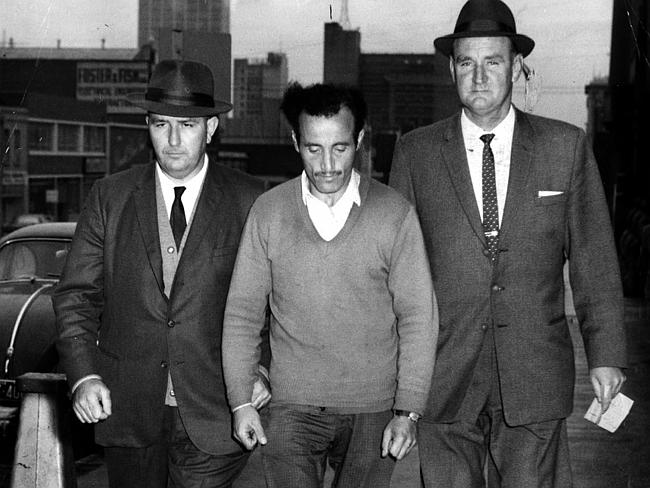 Detective sergeants James Black and Jack Ford bring William McDonald to police headquarters in Russell Street, Melbourne, after his arrest.