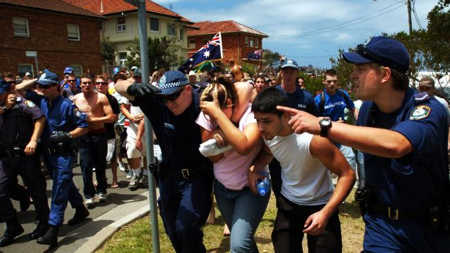 Police protect the innocent people from the angry mob. Picture: Craig Greenhill