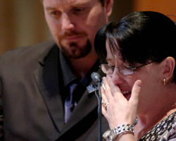 Sister of Constable Brett Andrew Irwin reads a eulogy for her brother while her Husband Ben provides support. Picture: AAP/Tony Phillips
