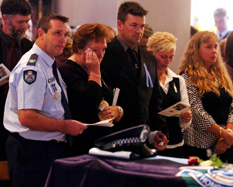 Ferny Grove Police station officer in charge Andy Graham (left) with Constable Brett Andrew Irwin's mother Chris Irwin (centre), brother Mick Irwin and family during the officer's funeral at the St Stephens Cathedral. Picture: AAP/Tony Phillips