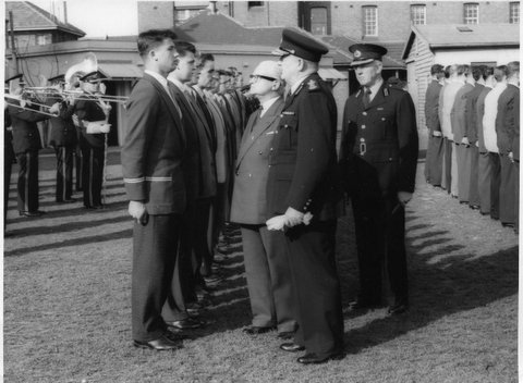 Cadet Barry Symons being addressed by Commissioner Colin J Delaney at a Passing Out Parade, approximately 1957. Next to Cadet Symons is Cadet Norm Maroney, No. 4 in the row is Cadet Terry Mathews. About No. 6 or 7 in the row is Cadet Max Mortimer.