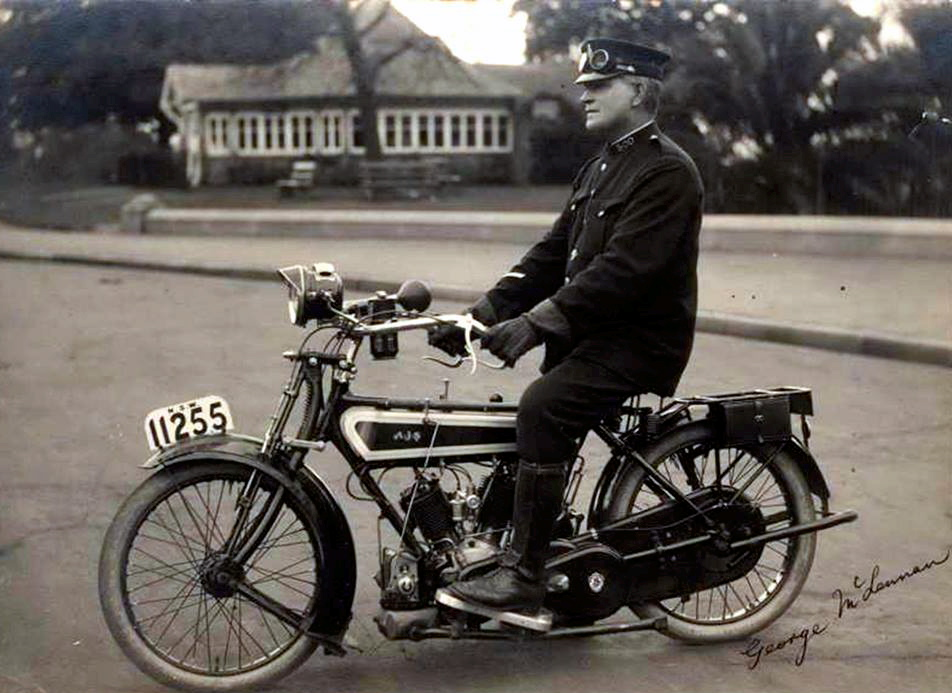 "Ref:168/97 George McLennan First NSW Police Motor Cyclist [On AJS Motorcycle. Outside Art Gallery Of New South Wales, Sydney] c1915. Silver gelatin photograph, captioned and annotated in ink on image lower right and verso, 14.1 x 19.4cm. Slight tear to right edge of image, minor stains, scuffs and silvering to image, laid down on old backing. Annotations include ""Born 2-10-1865, son of John Ross McLennan and Jessie (nee McIntyre). George died 6-11-1932, aged 67. He resigned from police force in 1925. Photographed outside NSW Art Gallery. Old Kiosk in background. It was later demolished to make way for the Cahall [sic] expressway."""
