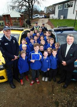 Winners are grinners: Sgt Michael Connors and WAW Credit Union's Peter Challis gave Wooragee pupils their prize yesterday. Picture: MATTHEW SMITHWICK