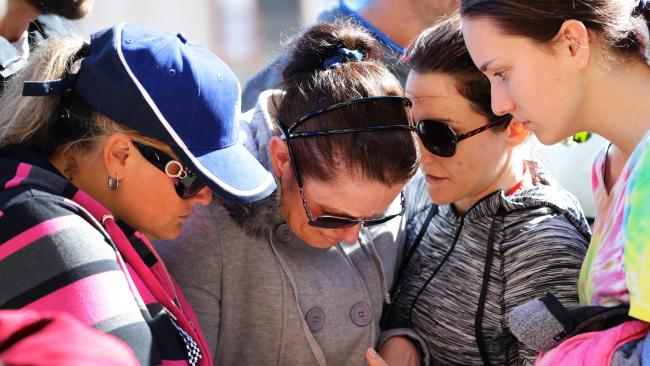 Susan Forte is supported by friends and family as she visits a makeshift memorial to her husband outside Toowoomba police station. Picture: Darren England<br />