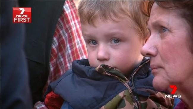 Brett's son Samuel, 3, is comforted at the Toowoomba police station memorial. Picture: 7 News Queensland<br />