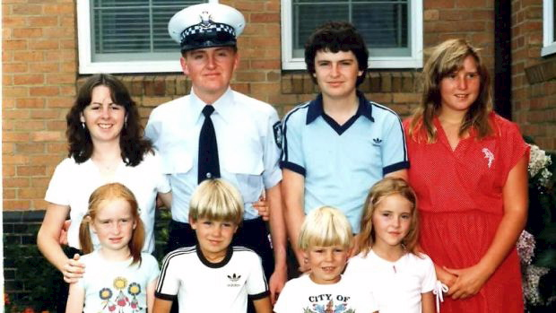 Ken Rich surrounded by his brother, sister and cousins on his graduation day from the police force. Photo: Supplied