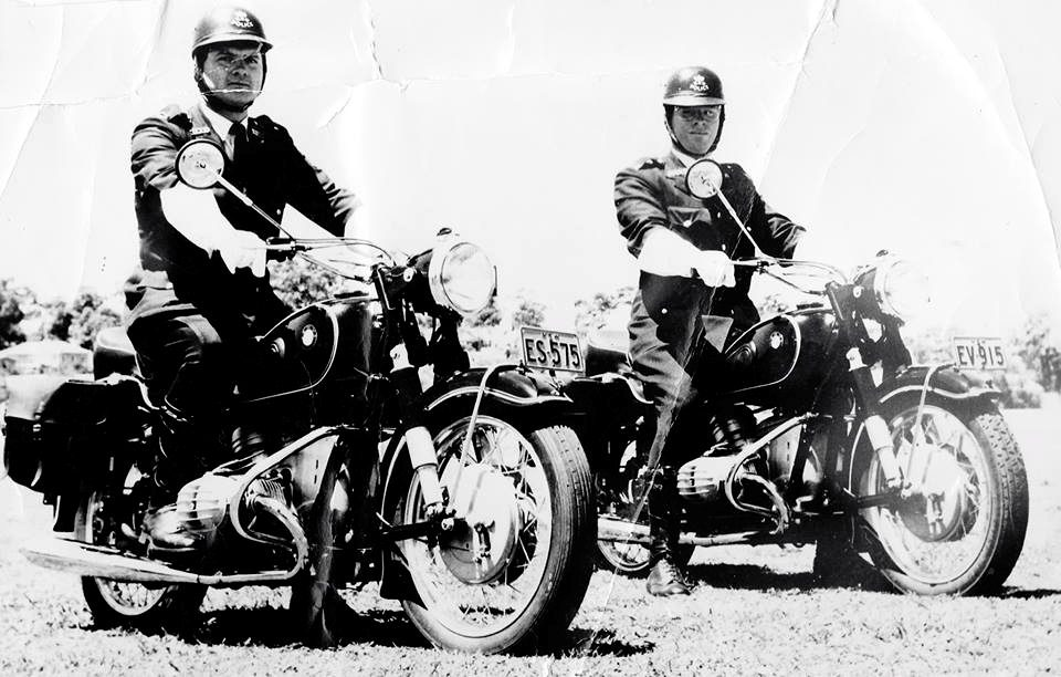 """John Burton Gibbs (right) riding Police cycle EV-915, with Noel Patmore, riding Police cycle ES-575, at Figtree Oval in 1961... the photo is captioned """"Escorting Mr Maloney"""" to Wollongong."""