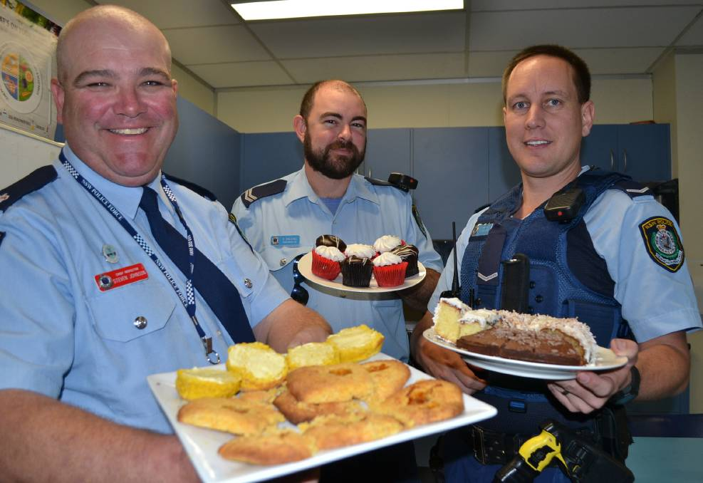SCRUMPTIOUS DELIGHTS: Shoalhaven LAC Chief Inspector Steve Johnson, Senior Constable Brian Balding and Constable Simon French with some of the delights from Thursday's morning tea.