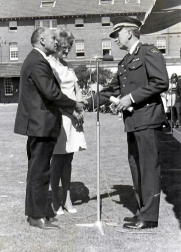 Donald and June Flavel accepting Certificate at the Robert John FLAVEL<br /> Donald and June Flavel accepting Roberts Graduation Certificate, his Police Cap, Epaulettes and Badge at the Redfern Police Academy - the day Roberts Cadet Class Passed Out ( Attested )<br /> Unknown Police Officer.