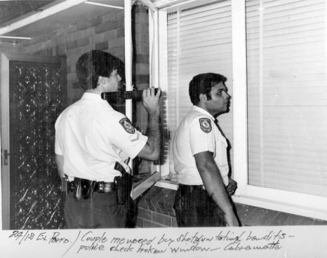 Cst 1/c Greg Callander & Constable Nabil Elias at a crime scene in Cabramatta where a couple were menaced by stotgun toting bandits. Around 1980.